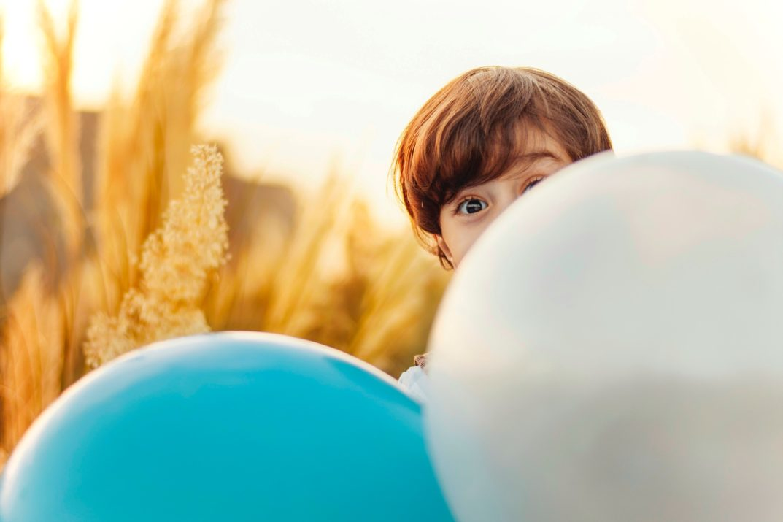 Photo by Ramin Talebi Kind hinter Ballons